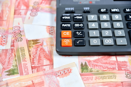 Black calculator lies with the Russian five-thousandth banknotes. Business still life
