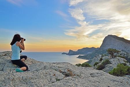Girl tourist photographing the landscape at sunset. Sudak. Crimea