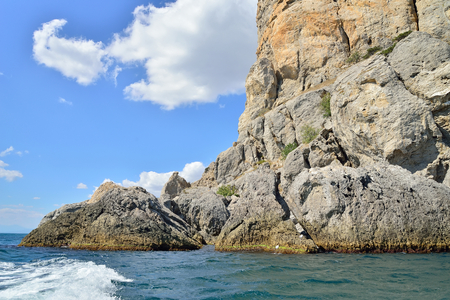 Wakes from boats on the backdrop of the cliffs. Crimea.. Sudak