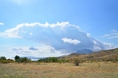 The cloud comes up from behind the mountains in the Karadag National nature reserve. Crimea