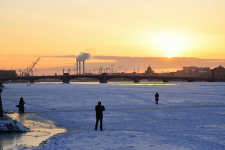 People take pictures of the Annunciation bridge at sunset in winter in Saint-Petersburg