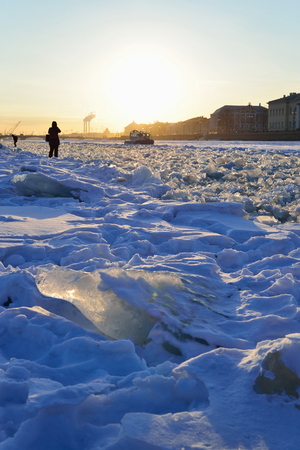 Snow-covered Neva river and boat MOE at sunset in Saint-Petersburg