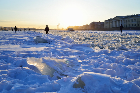 Snow-covered Neva river with ice floes and MOE boat at sunset in Saint-Petersburg
