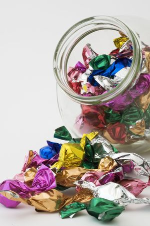 Candies in and around a glass candy jar Stock Photo