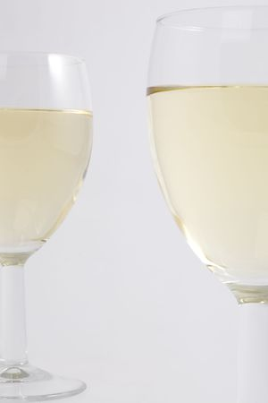Two glasses filled with white wine in detail.