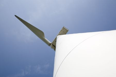 A single power generationg windmill against blue sky.