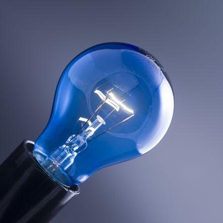 Blue burning lightbulb isolated against dark background