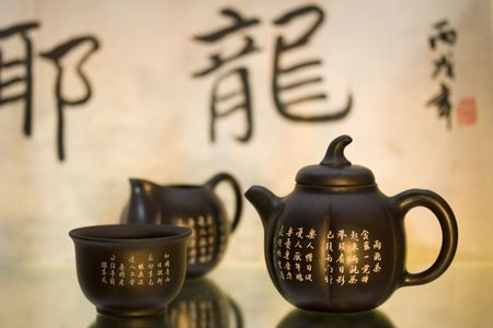 Black matte Chinese tea set with teapot and cup against a background of chinese characters and stamp