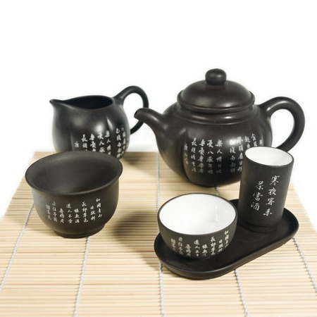 Black matte Chinese tea set with teapot and cup with chinese characters.