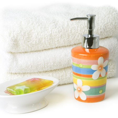 Colorful soap dispensor striped with  flower design and jelly soap. Small pile of white towels in the background.