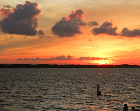 Bright sunset over water with pylans Stock Photo