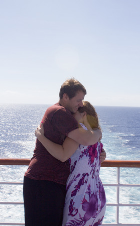 fantail: Honeymooners embrace at the fantail of their cruise ship