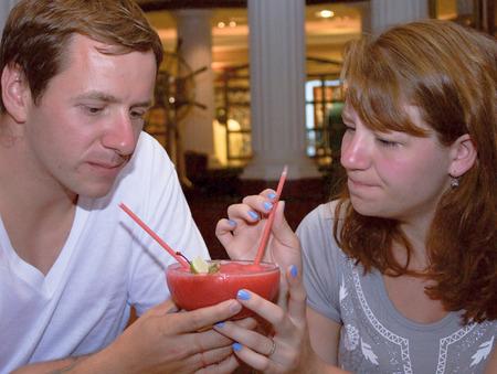 honeymooners: Thoughtful Honeymooners ponder over a strawberry daiquiri