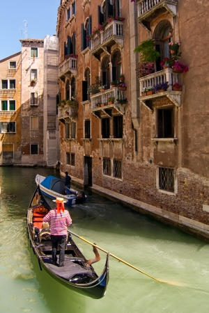 Gondolieri with gondola in one of venetian canals photo
