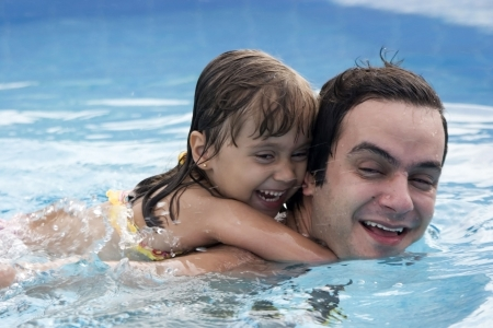Father playing with his daughter in swimming pool photo