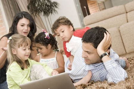 Portrait of family, mom, dad and their children enjoying indoor with a laptop Stock Photo - 4261231