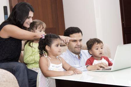 papa y mama: Retrato de familia, mam�, pap� y sus hijos disfrutan de interiores con un ordenador port�til Foto de archivo