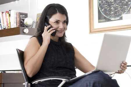 Professional woman working with telephone and laptop at workplace