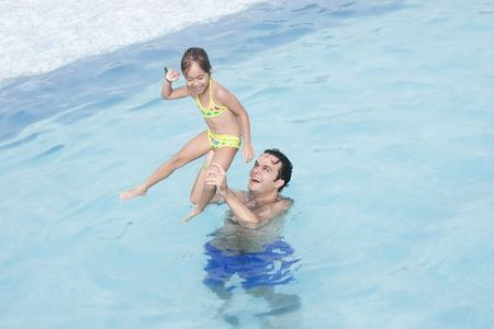 house float on water: Father and daughter in a swimming pool having fun