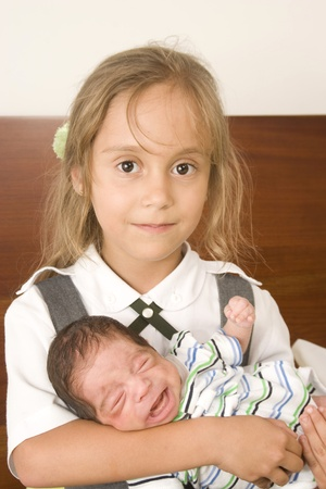 Beautiful girl and her little brother who is crying photo