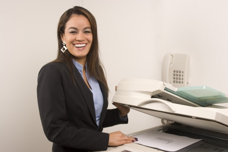 Young young businesswoman making copies on the photocopy machine at the office photo