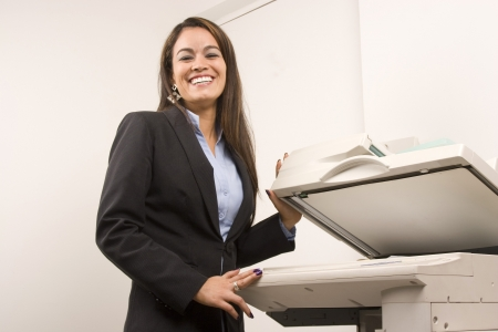 Young young businesswoman making copies on the photocopy machine at the office Stock Photo