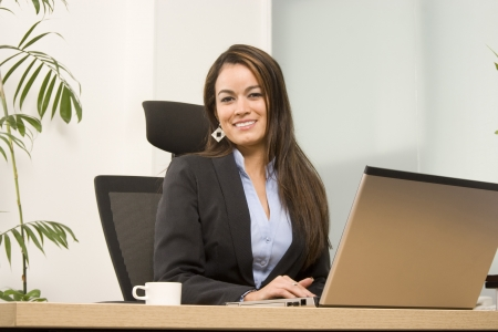 Businesswoman sits at a desk in front of a computer