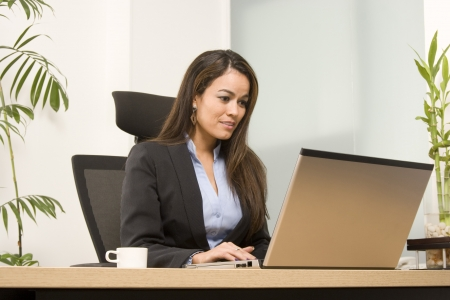 Businesswoman sits at a desk in front of a computer photo