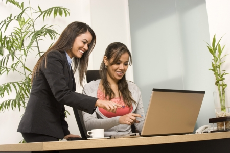 Two Businesswoman working together on laptop in office