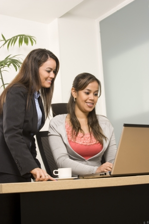 Two Businesswoman working together on laptop in office photo