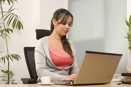 Businesswoman Working And Drinking Coffee In Front Of A Computer In Office photo
