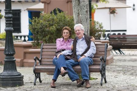 banc de parc: Vieux couple assis sur banc dans un parc