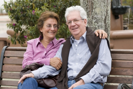 Senior Couple Sitting On Park Bench Outdoor photo