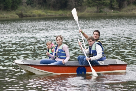 Happy Family, Uncle, Mother,Father and Daughter Canoeing on Lake Stock Photo