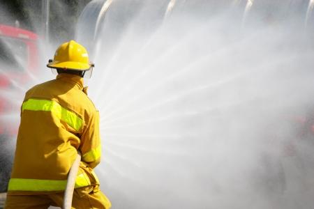 bombero de rojo: Bomberos que luchan por un ataque de fuego, durante un ejercicio de entrenamiento