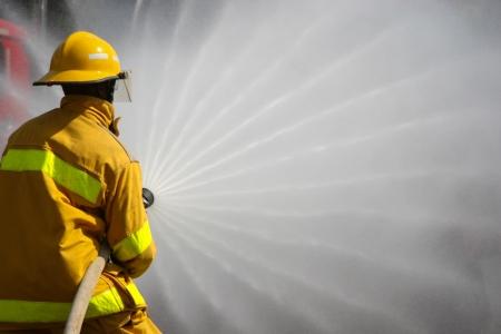 пожарный: Пожарные борются за огнем, во время учений