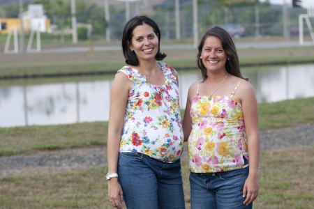 positiv: Portrait of Two Pretty Woman Holding Pregnant Belly , smiling over white Stock Photo