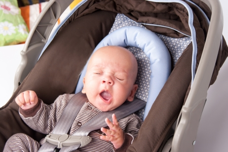 Portrait of a yawning baby Boy In Safety Seat photo