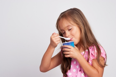 Adorable ni�a comiendo yogur photo