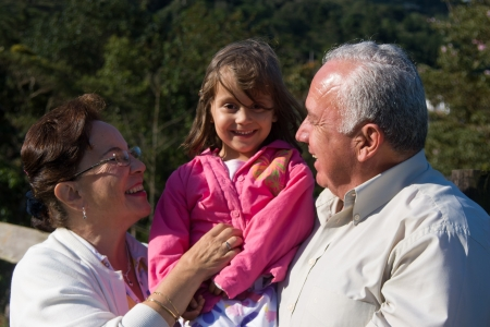 Happy Grandfather, Grandmother and grandchild, Enjoying At The Park