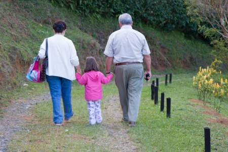 Happy Grandfather, Grandmother and grandchild, Enjoying At The Park photo