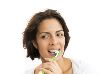 Portrait Of Attractive Woman Brushing Teeth In White Background photo