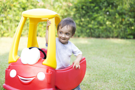 Happy Little Boy Driving His Toy In The Park photo