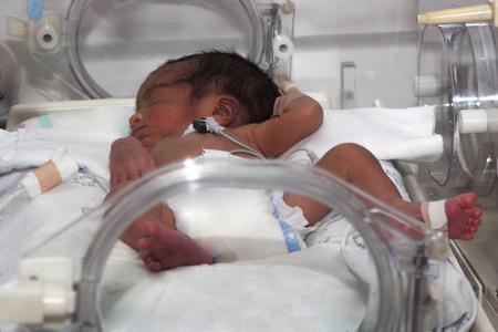 Portrait of newborn baby sleeping inside incubator