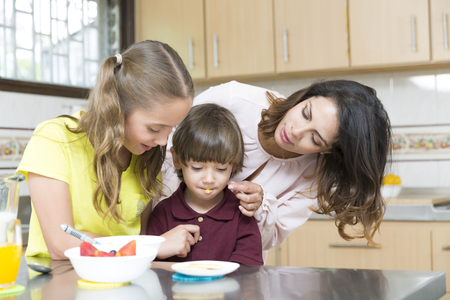 home health care: Lovely Mother and her children having breakfast in kitchen Stock Photo