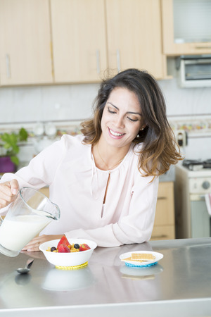 woman eating fruit: Attractive woman having breakfast in kitchen interior
