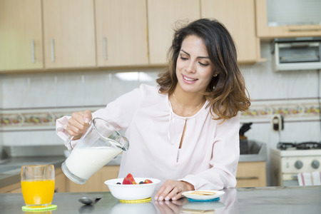 Attractive woman having breakfast in kitchen interior