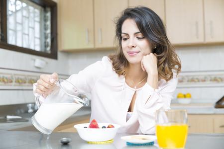 comiendo cereal: Attractive woman having breakfast in kitchen interior