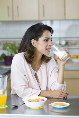 woman drinking milk: Attractive young woman having breakfast, drinking milk