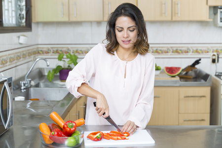 キッチンの美しい若い女性カット野菜 写真素材